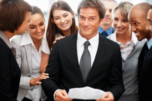 Colleagues looking at executives expression while he holds report