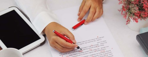 person proofreading a paper with a red pen