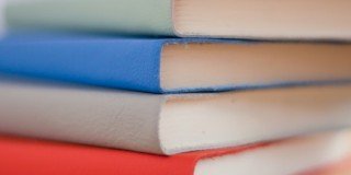four colored books stacked up