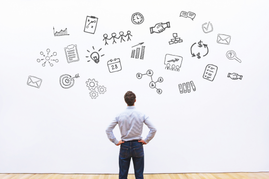 man staring at clip art symbols on a white wall